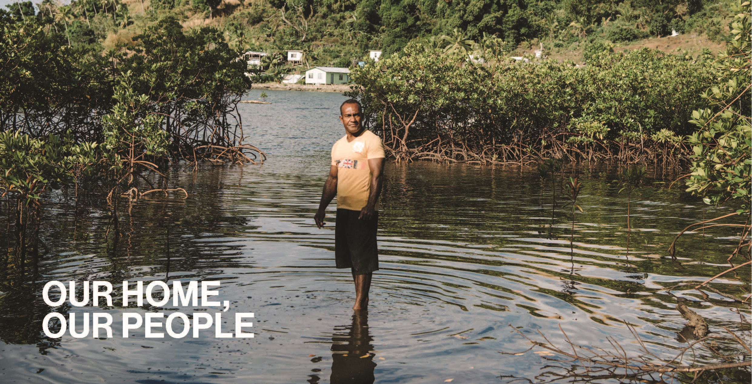 Fijian man standing in a flooded field in Fiji