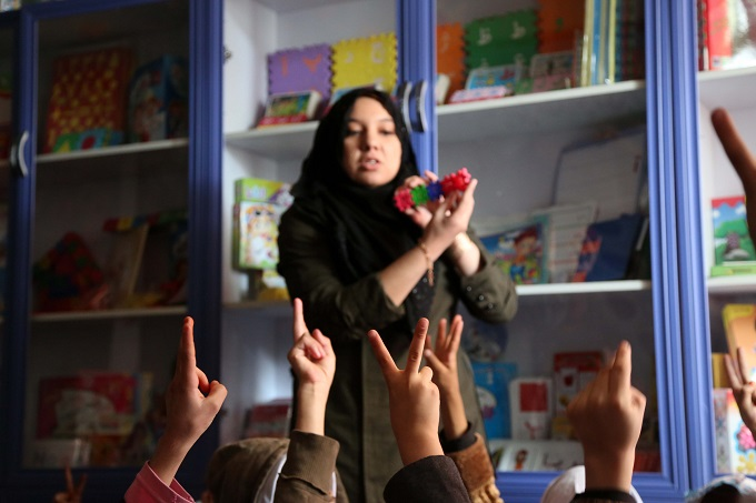 A primary school teacher in western Herat Province is teaching her students numbers with toys.