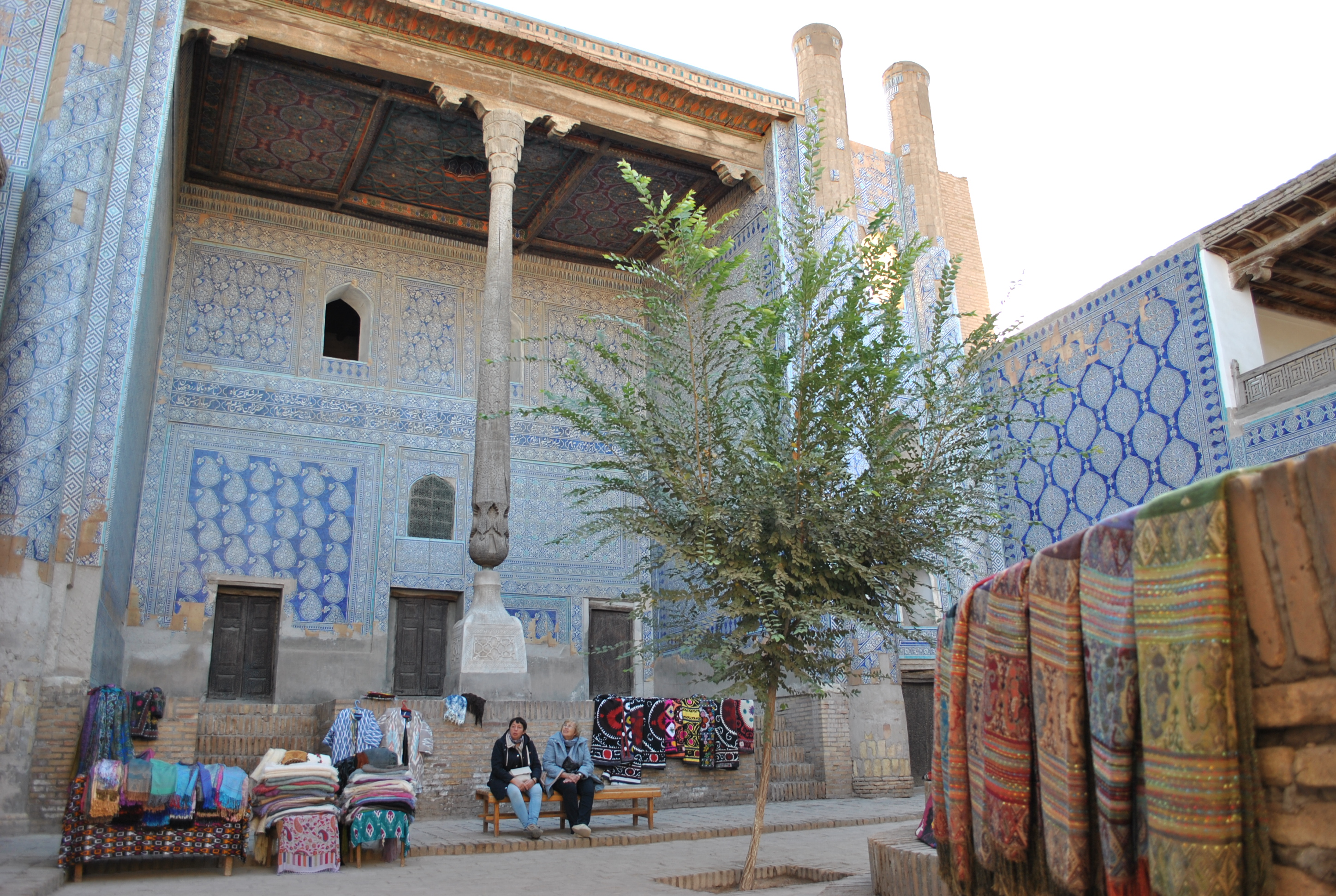 Visitors admiring Itchan Kala, the inner fortress of Khiva, full of craft vendors.
