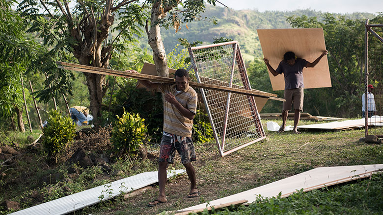 People from Namarai unload construction materials for new homes in the village. (Alana Holmberg/World Bank)