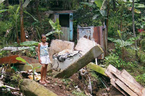 A young girl stands outside a home destroyed by a rainfall-triggered landslide in Castries, Saint Lucia.