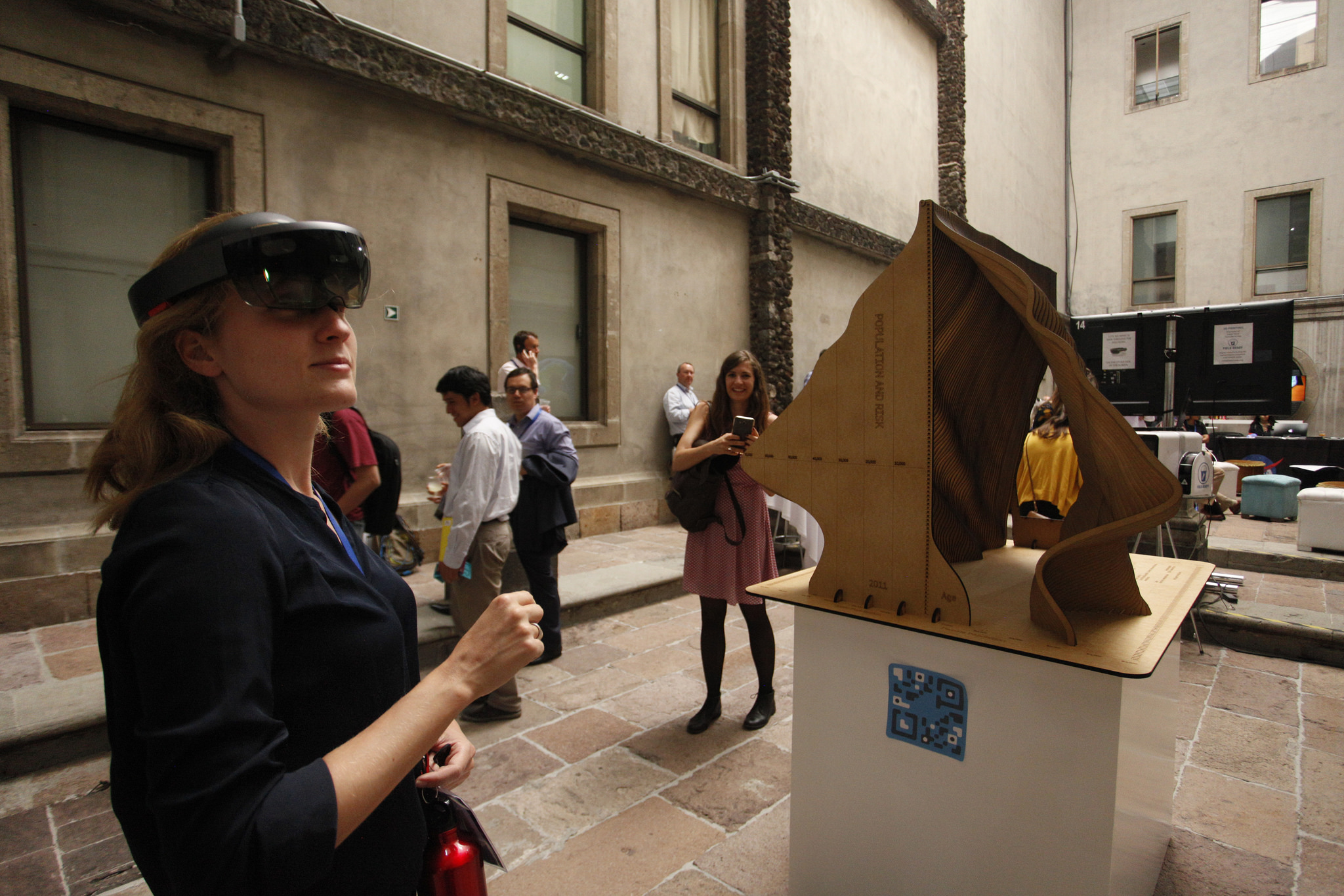A participant using Augmented Reality (AR) glasses to explore a data sculpture. The sculpture captured data on age over the last century. (GFDRR)