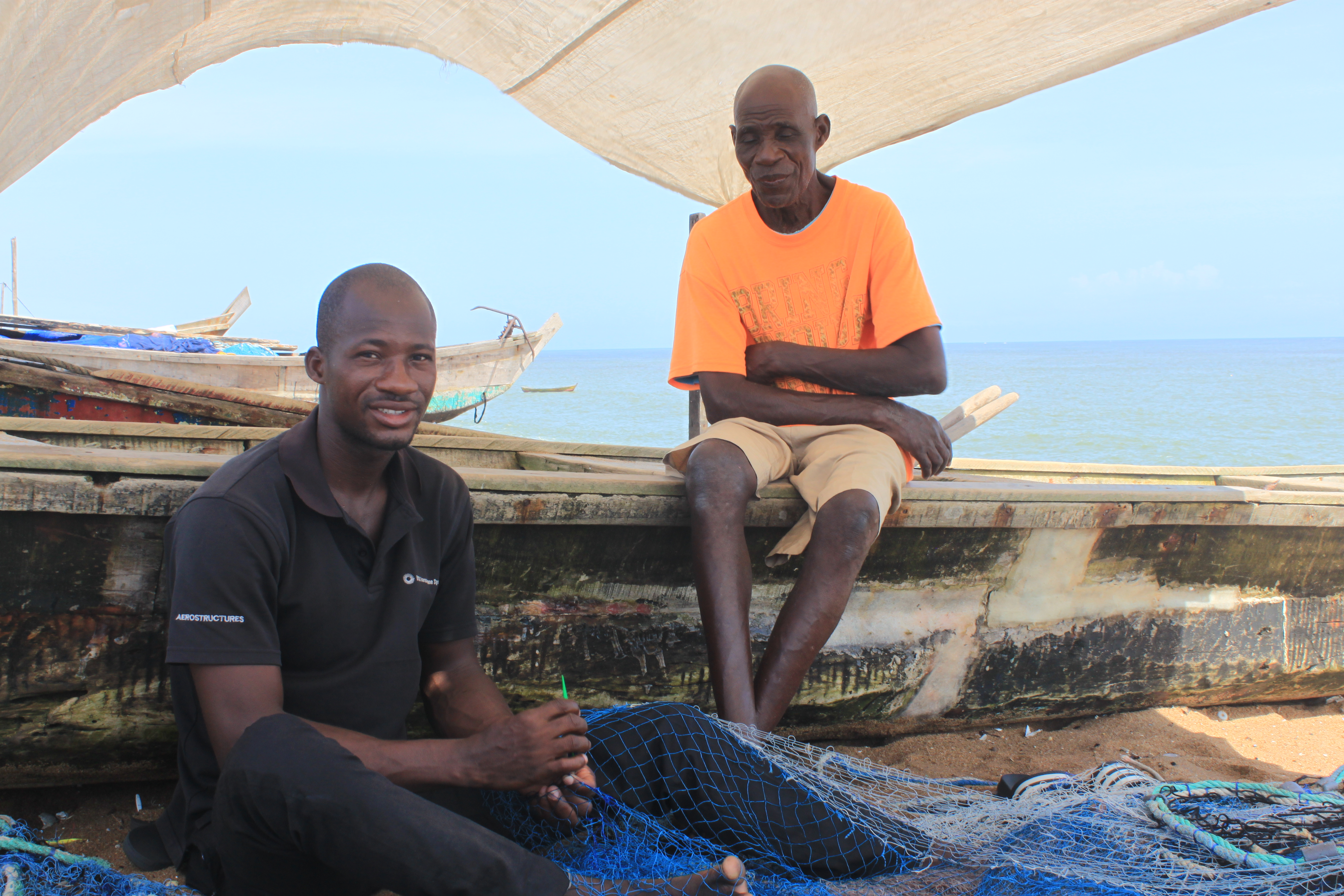 Fishermen work together, making nets to catch fish in Abidjan, Côte d'Ivoire