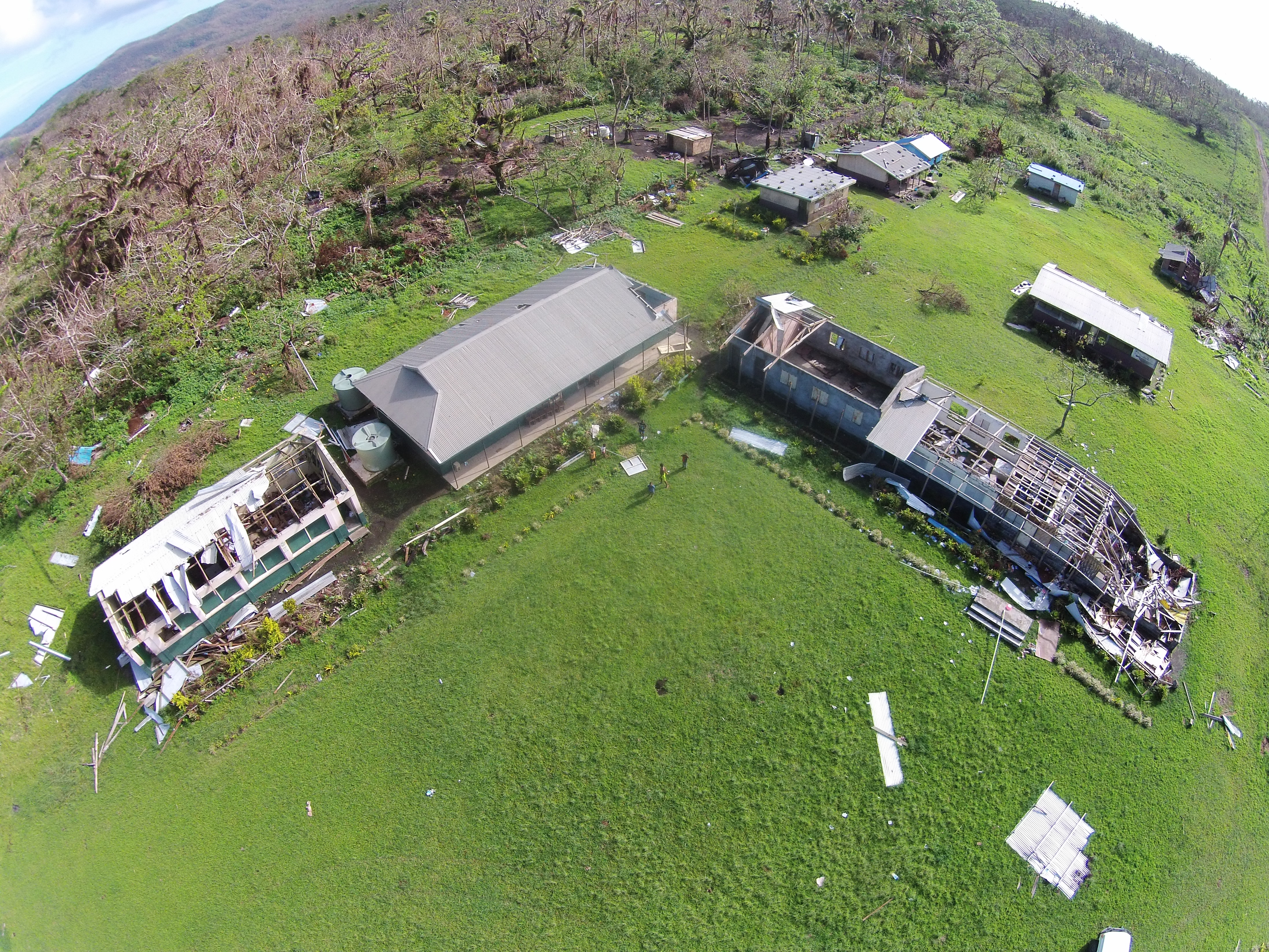 Aerial view of two school buildings with damaged roofs surrounded by debris from an extreme weather event.