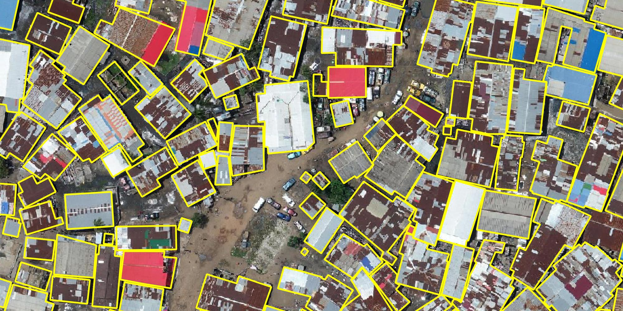 Aerial image of numerous buildings in a city, overlaid with yellow outlines to be used for digital mapping services.