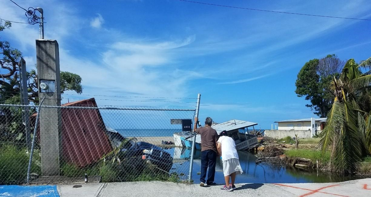two people survey wreckage after a hurricane in the caribbean