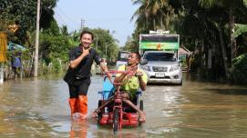 A volunteer in Southern Thailand helps a man with a disability get through a flood in his wheelchair.
