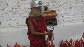 A monk learns to use a fire extinguisher hydrant.