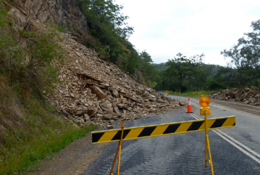 A small black and yellow barricade blocks off a road that has been damaged by a landslide